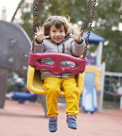 Young jubilant boy riding a yellow and red baby swing